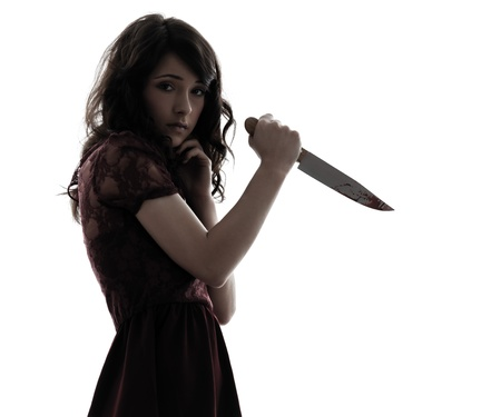 slasher: one caucasian strange young woman killer holding  bloody knife in silhouette white background Stock Photo