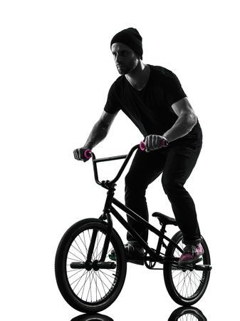 bmx bike: one caucasian man exercising bmx acrobatic figure in silhouette studio isolated on white background