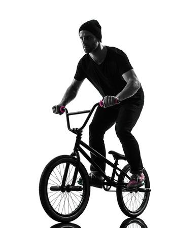 bmx bike: one caucasian man exercising bmx acrobatic figure in silhouette studio isolated on white background