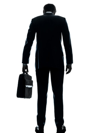 businessman standing: one caucasian business man sad standing rear view  in silhouette studio isolated on white background