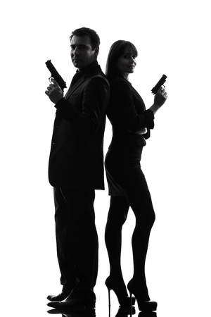 women with guns: one caucasian man detective secret agent criminal  with gun  in silhouette studio isolated on white background Stock Photo