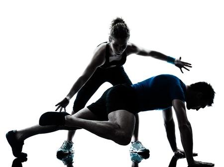hombres haciendo ejercicio: las piernas a una pareja el hombre cauc?sico mujer entrenador entrenador personal que ejercen silueta estudio aislado sobre fondo blanco