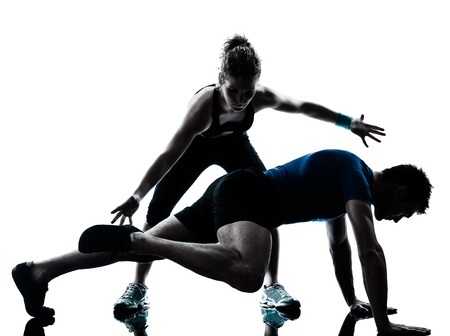 coach sport: one caucasian couple man woman personal trainer coach exercising legs silhouette studio isolated on white background