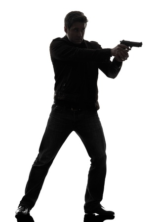 man holding gun: one man killer policeman aiming gun standing silhouette studio white background Stock Photo