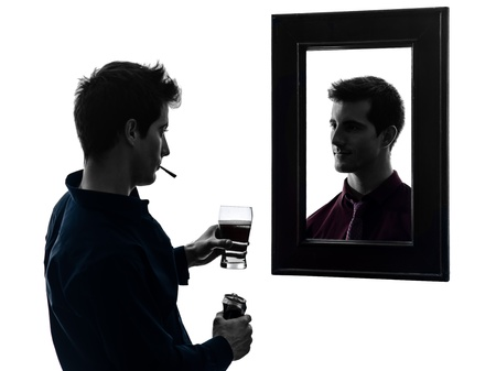 self worth: man in front of his mirror  in shadow  white background