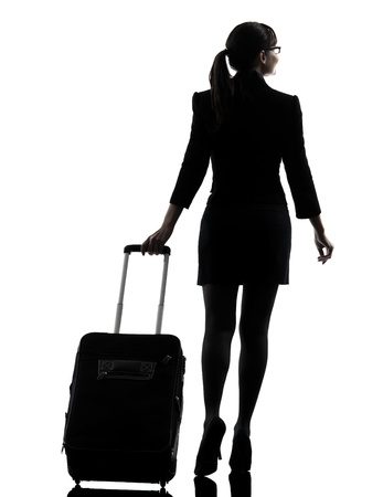 one business woman traveler walking  rear view  silhouette studio isolated on white background photo