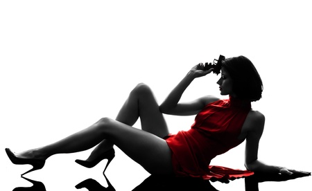 one sexy caucasian woman holding gun in silhouette studio isolated on white background photo