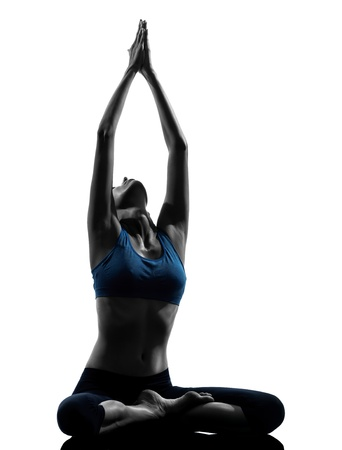 yoga silhouette: one caucasian woman exercising yoga meditating sitting hands joined in silhouette studio isolated on white background