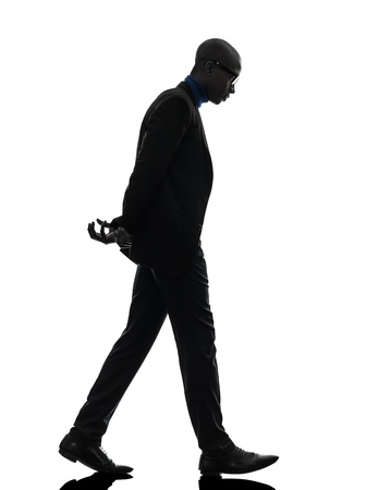 man looking down: one african  black man walking  looking down   in silhouette studio on white background Stock Photo