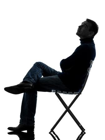 ülő: egy kaukázusi ember ül felnézett teljes hosszúságú sziluettje stúdió elszigetelt fehér háttér