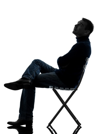 sitting on: one caucasian man sitting looking up   full length in silhouette studio isolated on white background Stock Photo