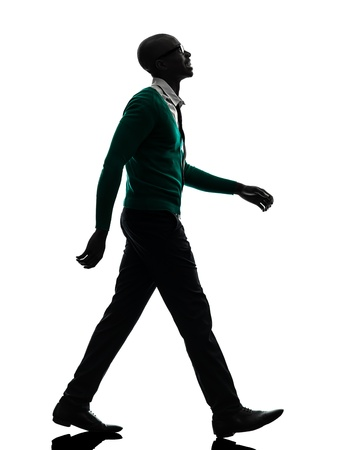 one african  black man walking looking up smiling  in silhouette studio on white background photo