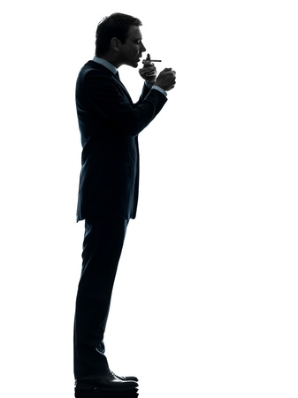 one caucasian man smoking cigarette  in silhouette studio isolated on white background photo