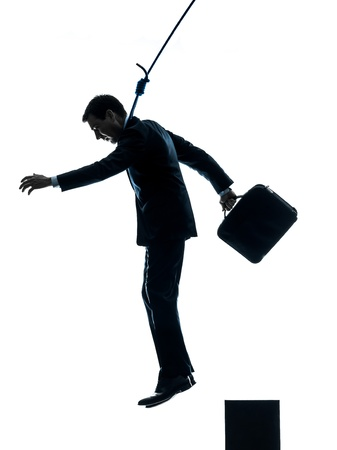 suicidal: one caucasian man business man suicidal hanging  in silhouette studio isolated on white background Stock Photo