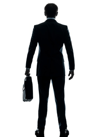 silueta masculina: un empresario de visi�n trasera de pie cauc�sica en el estudio de la silueta aislado en el fondo blanco Foto de archivo