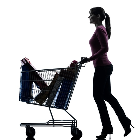 one caucasian woman with full shopping cart in silhouette studio isolated on white background photo