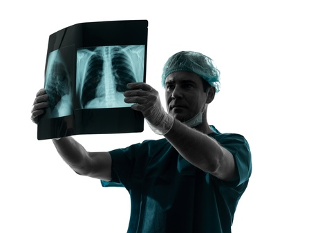 one caucasian man doctor surgeon radiologist medical examaning lung torso  x-ray image silhouette isolated on white background Stock Photo - 19533090