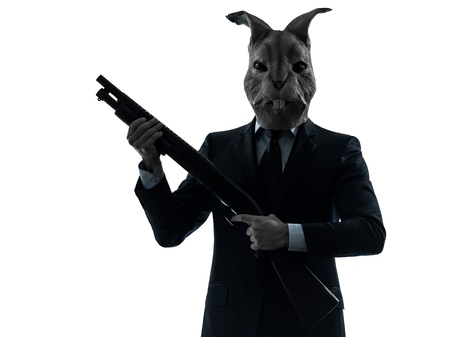 animal masks: one caucasian man rabbit mask hunting with shotgun portrait in silhouette studio isolated on white background Stock Photo