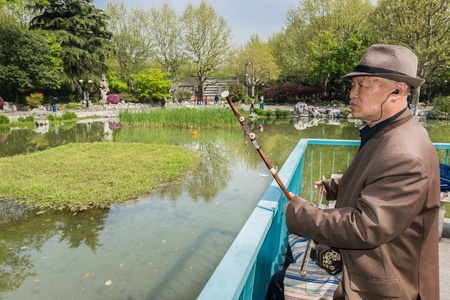 Shanghai, China - April 7, 2013  old man playing  er wu  traditional music instrument in fuxing park at the city of Shanghai in China on april 7th, 2013
