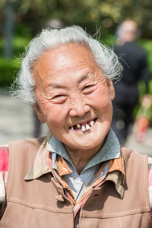 Shanghai, China - April 7, 2013 old chinese woman friendly toothless toothy smiling outddors portrait at the city of Shanghai in China on april 7th, 2013