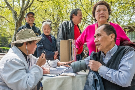 Shanghai, China - April 7, 2013  chinese doctor ausculting people  in fuxing park at the city of Shanghai in China on april 7th, 2013