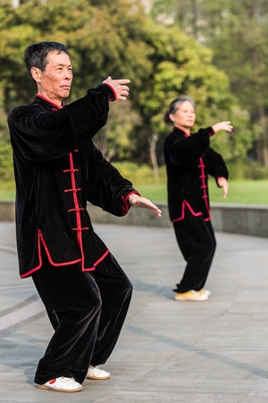 Shanghai, China - April 7, 2013  people exercising tai chi with traditional costume in gucheng park in the city of Shanghai in China on april 7th, 2013