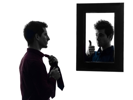 self esteem: man in front of his mirror  man in front of his mirror  in shadow  white background Stock Photo