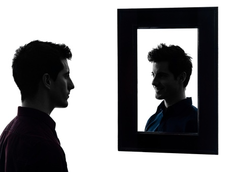 self worth: man in front of his mirror serious  in shadow  white background