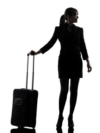 mujer con maleta: una mujer de negocios que viajan estudio de la silueta de pie aislado en fondo blanco Foto de archivo
