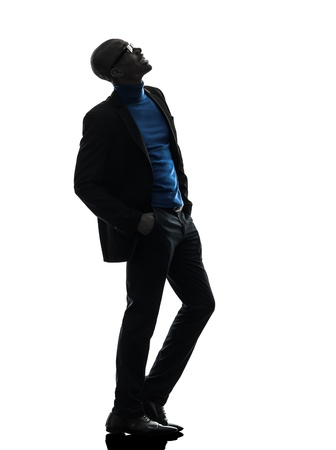 african american silhouette: one african  black man standing looking up  smiling   in silhouette studio on white background Stock Photo