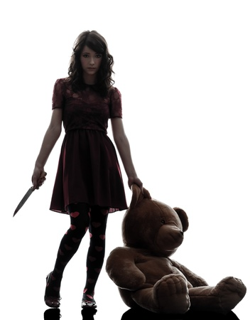 slasher: one caucasian strange young woman holding  bloody knife an teddy bear in silhouette white background