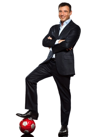 standing man: one caucasian business man standing arms crossed foot on soccer ball in studio isolated on white background
