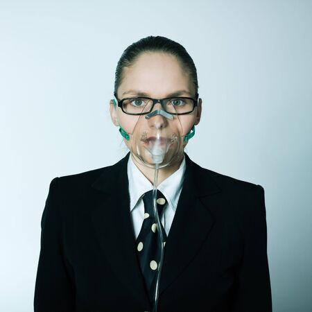 cut out device: studio shot portrait of one caucasian young breathless business woman  with oxygen mask