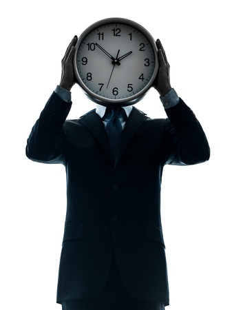 one caucasian businessman holding clock in silhouette studio isolated on white background photo
