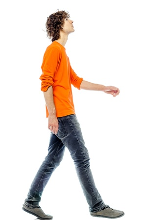 personas caminando: un hombre joven cauc?co caminando vista lateral mirando hacia arriba en el estudio de fondo blanco Foto de archivo