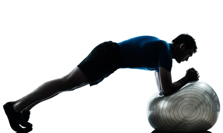 one caucasian man exercising workout fitness ball in silhouette studio  isolated on white background photo