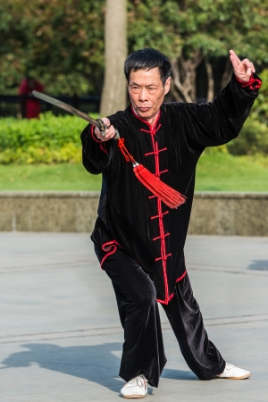 Shanghai, China - April 7, 2013  one man exercising tai chi with traditional costume in gucheng park in the city of Shanghai in China