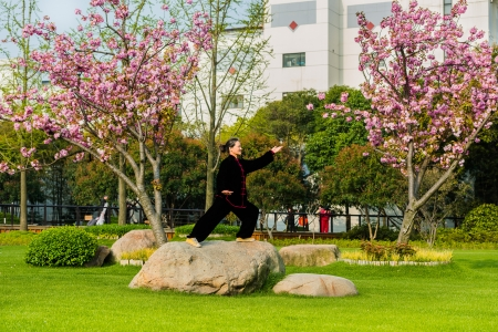Shanghai, China - April 9, 2013: one old woman  exercising tai chi with traditional costume in gucheng park in the city of Shanghai in China.