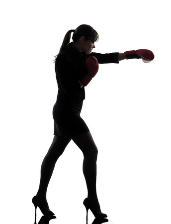one business woman punch g with box g gloves  silhouette studio isolated on white background