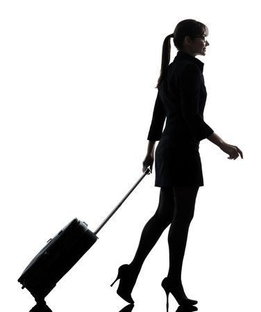 suitcases: one business woman traveler walking suitacse  silhouette studio isolated on white background