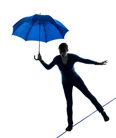 marcheur: une femme de race blanche tenant le parapluie en studio silhouette isolé sur fond blanc