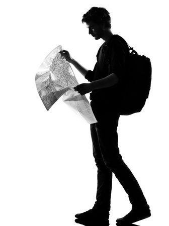 backpackers: young man backpacker reading map silhouette in studio isolated on white background Stock Photo