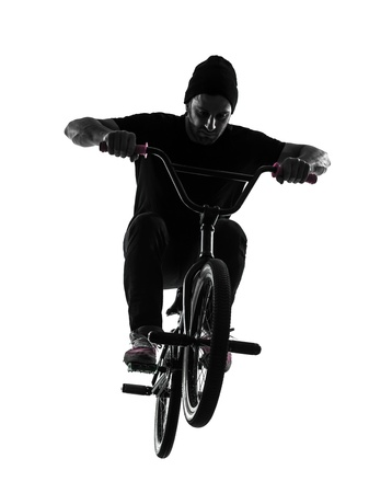 one caucasian man exercising bmx acrobatic figure in silhouette studio isolated on white background photo
