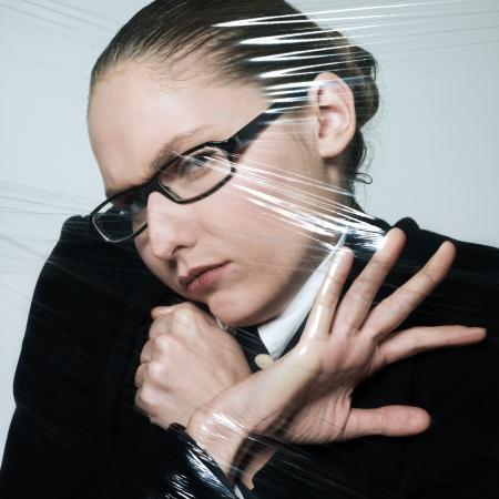 suffocating: studio shot ritratto di donna d'affari in plastica