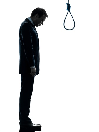 one caucasian man standing in front of hangman's noose in silhouette studio isolated on white background photo