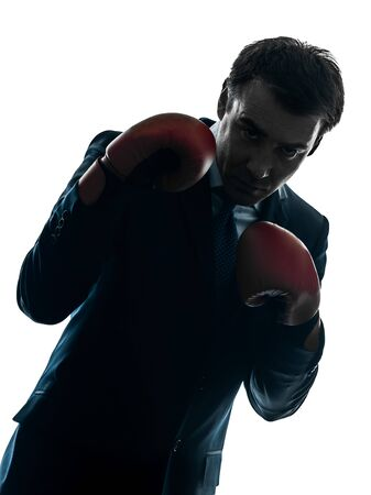 shadow silhouette: one caucasian businessman with boxing gloves   in silhouette studio isolated on white background Stock Photo