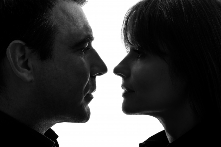 emotion faces: one caucasian couple woman man face to face in silhouette studio isolated on white background