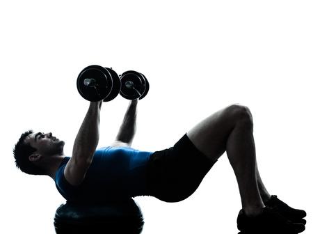 levantamiento de pesas: un hombre cauc?sico ejercicio de entrenamiento con pesas en el entrenamiento de la aptitud bosu en el estudio de la silueta sobre fondo blanco Foto de archivo