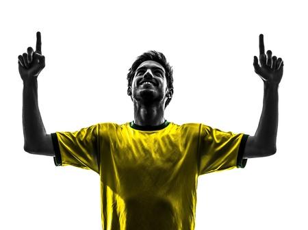 indoor soccer: una brasile�a de f�tbol jugador de f�tbol joven felicidad hombre apuntando en estudio de la silueta sobre fondo blanco