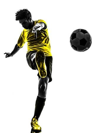 fútbol jugador: una brasile�a de f�tbol jugador de f�tbol joven patadas en estudio de la silueta sobre fondo blanco
